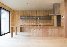 クライアントのナチュラルな色の木材に囲まれた生活をしたい。というご希望を叶えるため天板に集成材を採用し、側面にリビングで採用している床材を施工することとしました。さらに、天板がそのまま大きなダイニングテーブルとなるように、足元に100mm程度の段差を設けることでキッチンの天板とフラットに繋がる形状としています。このシンプルでフラットな形状のキッチンにアクセントとしてスプリング状にデザインされている