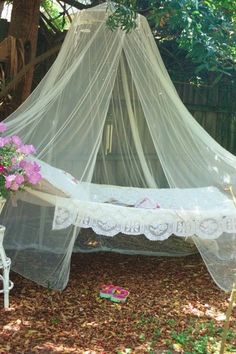 This comfy hammock in the garden, adorned with lace, pillows and surrounded with sheer curtains would be a nice place to read a book or take a nap.