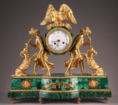 A gilt bronze and malachite mantel clock representing two feminine characters supporting on their back the dial surmounted by a vulture with spread wings.