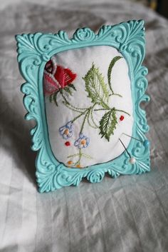 Framed embroidery puffed to serve as a pincushion