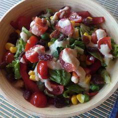 Ensalada de lechuga, pimiento rojo, tomates cherry, maiz y pasas