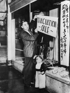 Japanese-American Merchant Posts a Sale Sign on His San Francisco Store, 1942