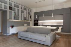 aménagement salon salle à manger - canapé gris clair, armoires de cuisine en blanc et gris, table et chaises blanches