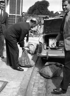 1963: Police officers put bags of evidence into a car boot after the Great Train Robbery.