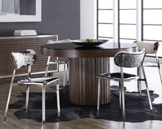 JAKARTA DINING TABLE   Reminiscent of old world styling, this round dining table from our ikon collection features an etched base crafted from solid espresso wood. Black tempered glass rests atop the table for a clean, transitional look.