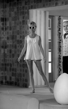 Brigitte Bardot. White Sleeveless baby doll dress, worn over short shorts, square white tinned sunnies, summer, messy bun
