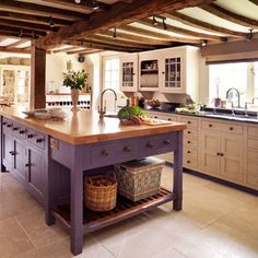 Splash of colour in an otherwise neutral scheme. Beams and wicker baskets lend a country feel.