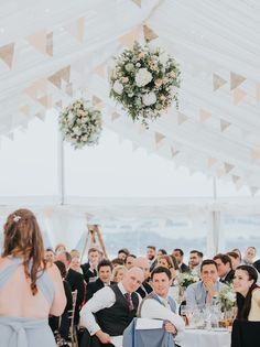 Soft pastel bunting and toning flower ball hung from the roof of the marquee - beautiful