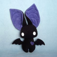 Poor Dexter was born a little oddly proportioned, with big, big ears and wings too tiny for flying. Luckily his friends dont really mind carrying him around. Wont you be his friend too? Dexter is approximately 9 inches tall from toe to forehead (not counting his ears) and 10 inches wide from wingtip to wingtip. He is made with black and violet purple fleece, has embroidered details on his ears and wings, and is stuffed with hypo-allergenic polyfil. His felt eyes and heart are…