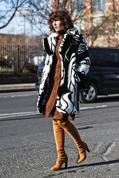 A printed fur coat is worn with a suede dress and over-the-knee boots