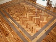 Australian cypress wood floors with a herringbone pattern, bordered by a double band of walnut floorboards