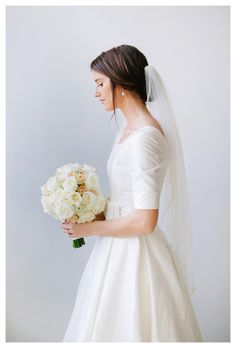 Pretty modest wedding dress with elbow sleeves and veil.