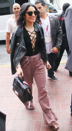 Vanessa Hudgens wears a black lace-up bodysuit with a leather jacket, layered necklaces, pink wide-leg trousers, and a black top handle bag