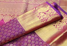 A rich plum purple pure kanchipuram silk saree with a stunning broad border of mango/paisley design and burnished gold. The body and pallu/fall of the saree are richly adorned with traditional zari designs.