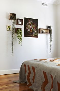 Hanging plants (these appear to be string-of-beads, Senecio rowleyanus,) and a couple of pictures make striking wall arrangement. Just make sure theres enough light for the plants.