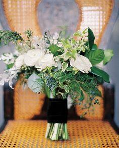 White ranunculus, flat cedar, holly, rosemary, and seeded eucalyptus bound with plush velvet ribbon