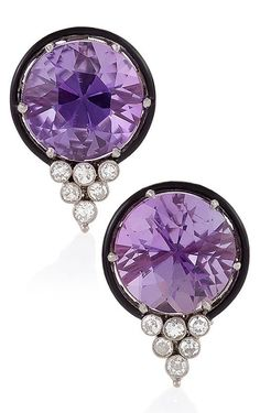 A pair of Art Deco platinum amethyst and diamond earrings, 1930s. Each earring centring a round amethyst weighing approximately 6.00 carats, surrounded by a ring of black enamel with a diamond-set triangular motif below, mounted in platinum.