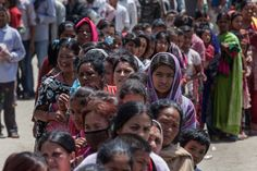 Residents line up for food in an evacuation area set up by the authorities in Tundhikel park on April 27, 2015 in Kathmandu.
