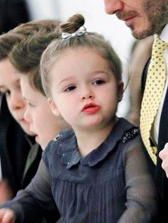 Love Her Hair! | HARPER BECKHAM | We know: cutest photo ever. Once you're done saying aww, check out Harper's perfectly executed top knot (it's her signature look) adorned with a metallic bow.