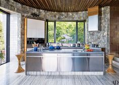 The kitchen, which features walls of local stone, is equipped with a Miele microwave oven, espresso machine, and vent hood; the cabinetry and quartz-top island are by Poliform.