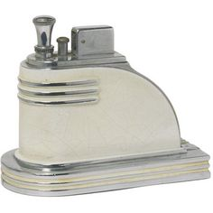 The streamlined shape of this Ronson cigarette lighter was a feature of the American Art Deco style. This piece was made about 1925 when American designers applied streamlining not just to means of transportation such as trains and motorcars but also to architecture and a wide range of consumer goods. Streamlining allowed designers to create a modern decorative style.