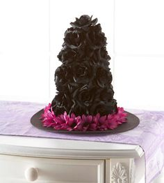 Embellish a plain witch's hat with black silk flowers and other Halloween bling