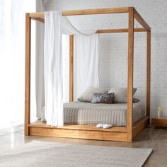 Simple wood canopy bed. I'd prefer even thicker posts. It's good that it's light though, dark wood canopy beds visually take up much more space.