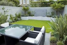 Garden Decor With Small Garden Design A Modern Design Garden Landscaping Design Equipped Four Seats Behind Home White Sofa And Glass Table Fenced Grass Gray Wall of Amazing Modern Garden Design To Beautify Your Lovely Home from Exterior Ideas