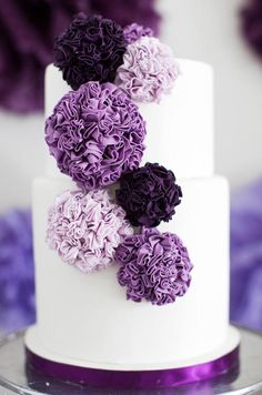 Handmade gumpaste pom-poms in rich purple hues top a clean white cake. Read an interview with this baker, Sophie Bifield.