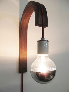 """Bent lamination wall sconce in walnut or ash. Handmade in Brooklyn, NY. Includes wood sconce, fabric covered cord with switch, and chrome-bottom bulb. Sconce measures about 14"""" tall and sticks out from the wall about 9"""". (Please allow 2-3 weeks for delivery as they are made to order)"""