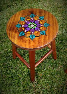 Banqueta de madeira com pintura de mandala, feita a mão, no assento. Acabamento em verniz brilhante. **ATENÇÃO! Novo modelo tem as pernas quadradas e não mais redondas como na foto! Continua linda e com a mesma qualidade!!** Pode ser usada como mesa lateral ou criado mudo também. Uma graça! Cores do desenho: turquesa, roxo, rosa, laranja, verde, preto. - 6FB513