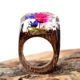 HIDE IN THE THICKET AND FIND THE FLOWER THAT IS WAITING FOR YOU TO PICK IT. This ring is made of green resin. The base is a dark walnut wood, known for being strong, durable, and beautiful.