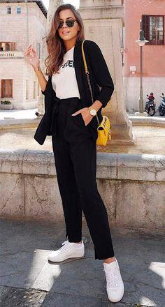 Look com calça clochard preta, blazer preto, t-shirt, tênis branco e bolsa amarela.