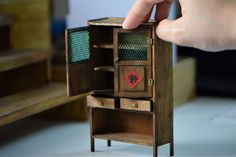 Old miniature village cupboard dollhouse furniture Scale: 1/12 Size: 77mm x 31mm x 128mm (LxWxH)  The old village style wooden cupboard is perfectly fit into your countryside kitchen! The size of cupboard I designed can also fit in all kind of my miniature plates and bowls!  The doors and drawers can be opened.  It is made of high quality bass wood and painted in teak color.   Note to buyer: - Only ONE wooden cupboard is included in this purchase, other accessories are just for photograp...
