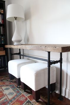 Black steel console table topped with a weathered yet solid plank