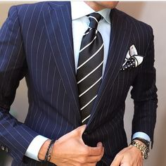 Navy pin striped suit, striped tie, white shirt and Polka dot pocket square.