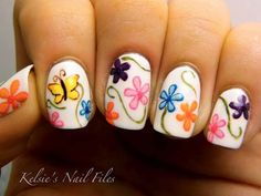 This butterfly nail art design looks very fun to work with. The design is simply painted with a matte white base color along with colorful flowers on them, thin curves of green and fluttering butterflies all over the nails.