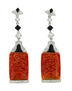 A pair of carved coral, black onyx, and diamond earrings  carvings of deer motif; mounted in eighteen karat white gold;