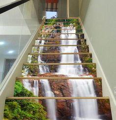"""""""Vinilo para escalera cascascada de Aj Wallpaper"""" Una opción para decorar escaleras de una casa de dos pisos o un loft, como éstas situadas en un lateral del salón con barandilla de cristal."""