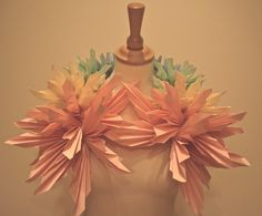 Over sized hand folded paper neck piece in pastel pink, yellow, green and blue, used as a display piece