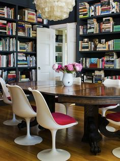 Tulip chairs, clawfoot mahogany table, floor-to-ceiling black bookcases, capiz chandelier