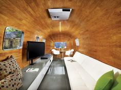 The long sofa, bar, and television were obvious choices for a pre-show hangout, but how to achieve the continuous curve of the revamped Airstream's interior was not. Baldridge and his team labored to find a kind of wood that would accept the serious bend before hitting on mahogany veneer.    Read more: http://www.dwell.com/articles/trailer-flash.html##ixzz25pQzKplt