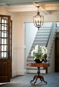 Dark stained double doors open to an absolutely gorgeous foyer featuring a coffered ceiling accented with an antique brass lantern hanging over a round antique table topped with orchids.