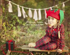 girl-in-Christmas-pajamas-with-red-green-elf-hat-on-vintage-wooden-rustic-sled-in-natural-light-photography-at-cedar rock-park-burlington-nc-chapel hill-children's-photographers