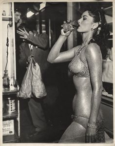 The Gold Painted Stripper (ca. 1950)  Weegee  Many of Weegee's Hollywood photographs take the viewer backstage or behind the scenes. In this photograph, an offstage burlesque dancer in shimmering body paint pauses for a drink while the figure in the background shields his face from Weegee's flashbulb.  International Center of Photography, Bequest of Wilma Wilcox, 1993 © Weegee/International Center of Photography/Getty Images