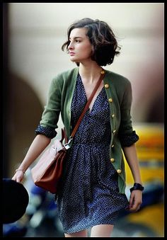 what a cutie! love the green cardigan paired with the blue print dress. satchel is a nice touch and her hair is really great too