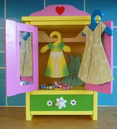 Paper folded origami dresses hanging in a wood toy wardrobe