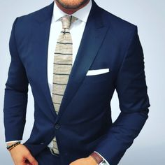 Striped knit tie and navy blue suit.