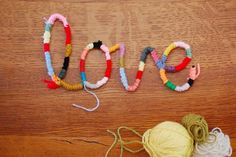 """Wrap yarn around rope and """"write"""" a word with the rope. Stitch the rope where it crosses to hold together, and glue to a board for fun wall art."""