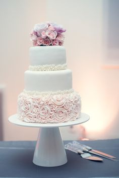 Gorgeous cake with varying sizes of sugar (or maybe fondant) pearls and a bottom layer of buttercream roses with a mini floral pattern to fill in between them.